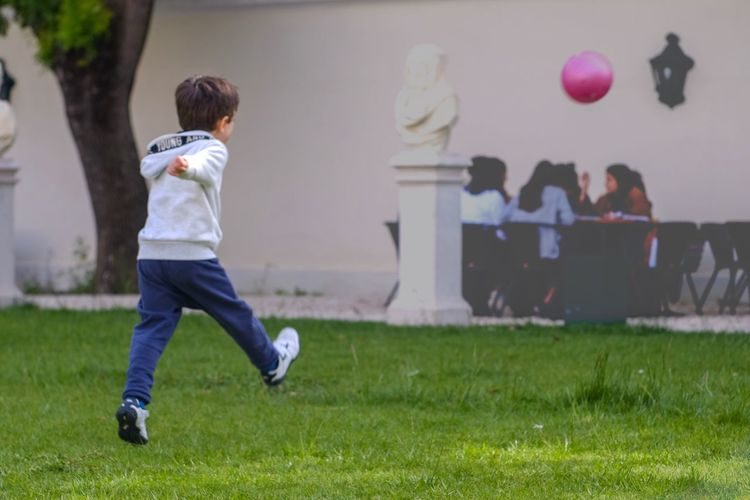 Rear view of boy playing with ball at park