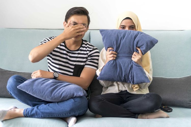 Young Malay Couple at the Sofa watching scary movie cover their eyes Sitting Full Length Two People Casual Clothing Males  Togetherness Real People Lifestyles Men Indoors  Front View Child Leisure Activity Boys Childhood Sofa Furniture Women Family Young Women Son