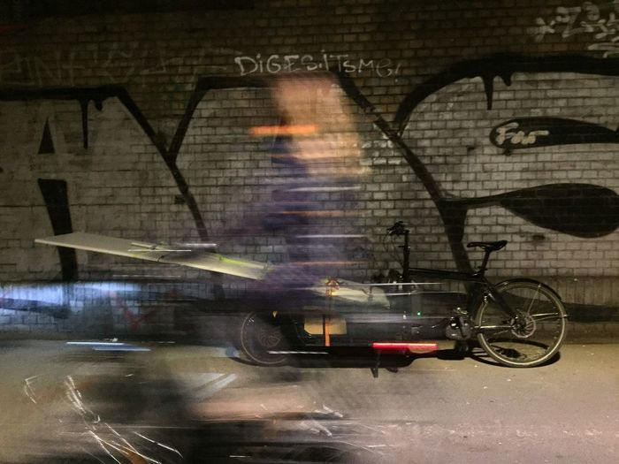 Blurred motion of man riding bicycle on street in city