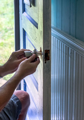 A man is replacing a door handle and lock on an outside door