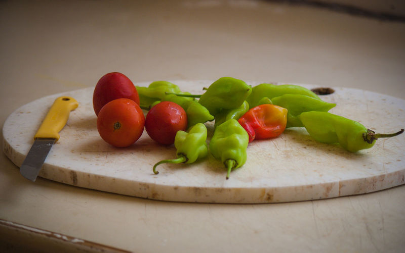 Close-Up Of Tomatoes And Green Chilies On Cutting Board
