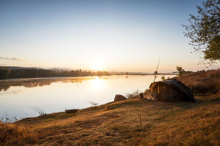 Abandoned ship on lake against sky during sunset