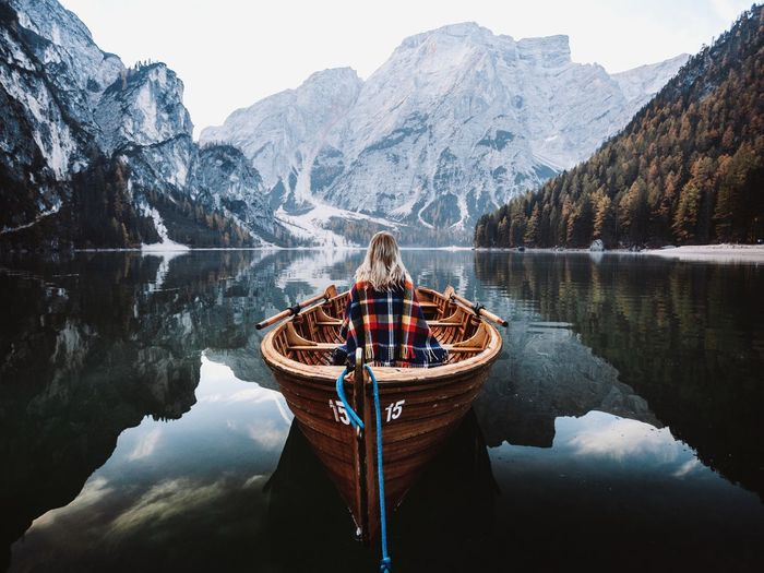 Rear view of woman in boat on lake against mountains