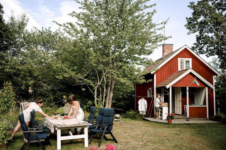 People sitting on table in yard against house