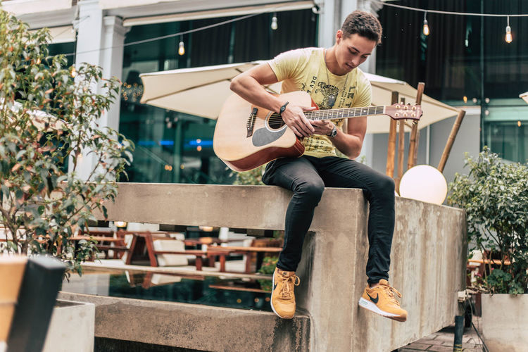Young man playing guitar while sitting on railing