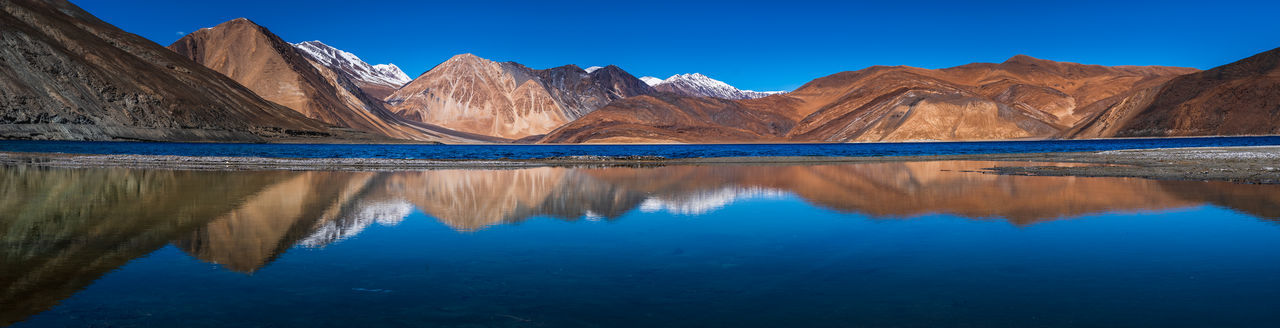 Reflection of mountain range in lake against clear blue sky