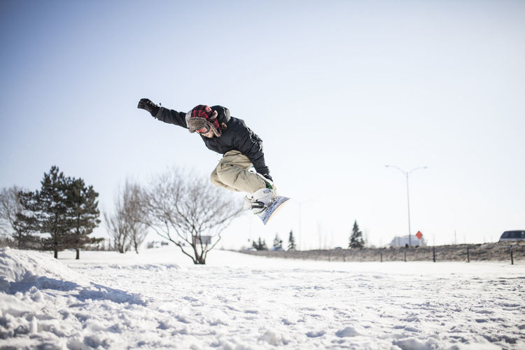 Man jumping in snow on field against sky