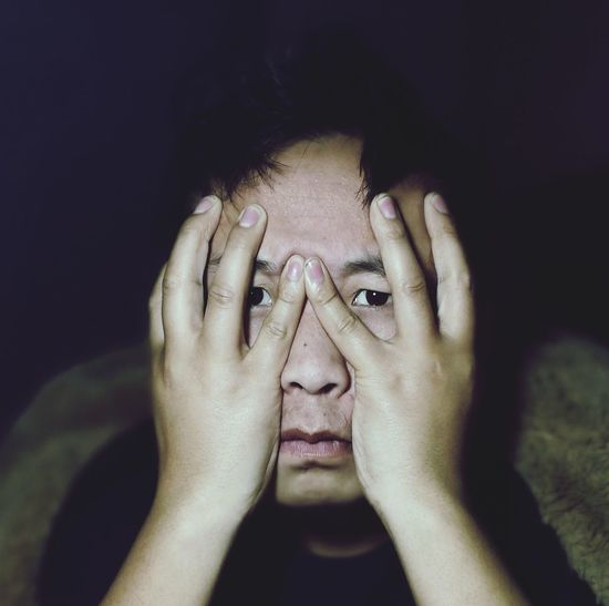 Close-up portrait of man covering face at night
