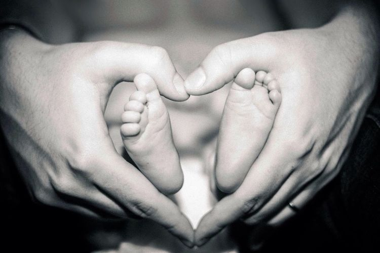 Close-up of hands holding feet of baby