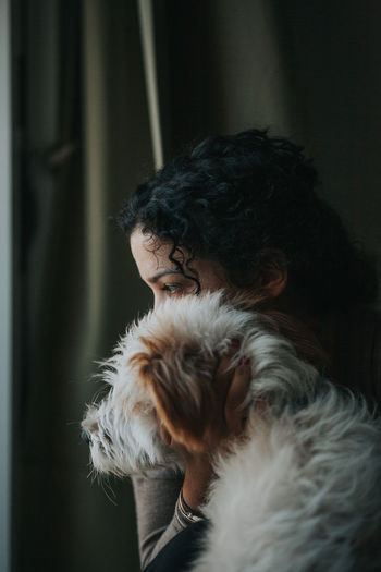 Close-Up Of Woman Holding Dog At Home