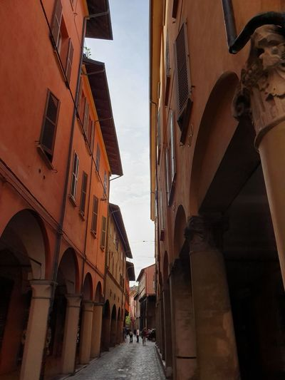 Low angle view of narrow alley amidst buildings in city