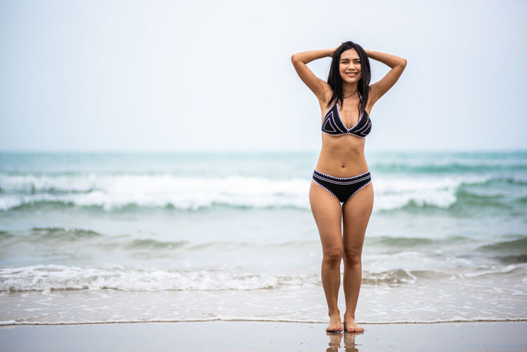 Sea Land Beach Water Young Women Young Adult Clothing Standing Women One Person Swimwear Bikini Beauty Beautiful Woman Full Length Leisure Activity Focus On Foreground Horizon Over Water Hair Human Arm Arms Raised Hairstyle