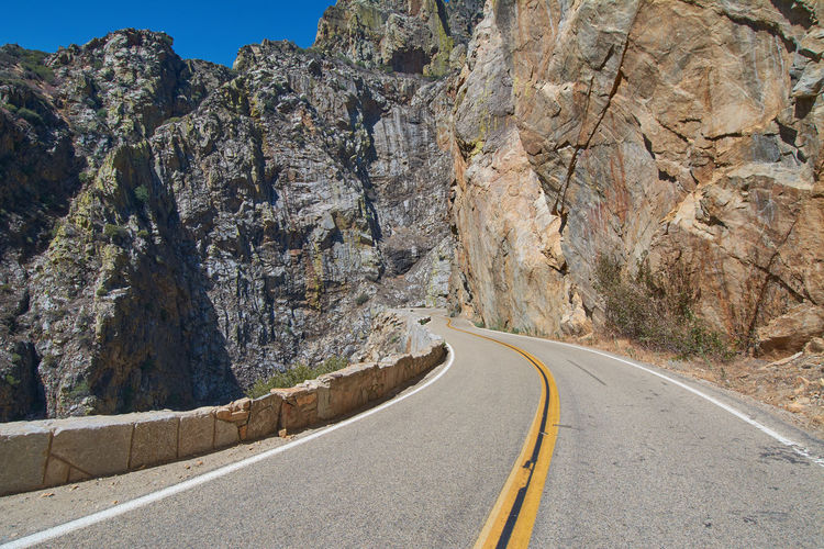 Road amidst rocky mountains against sky