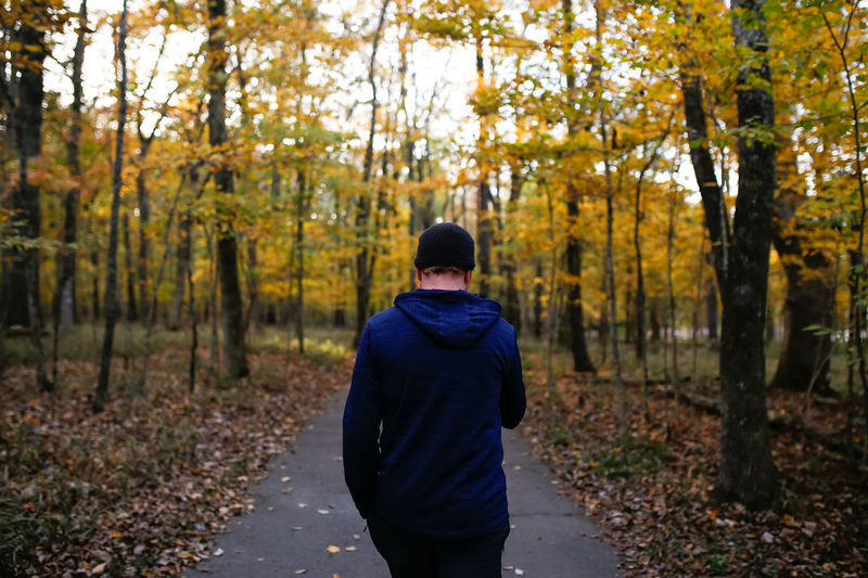 Man walking down nature trail during autumn Autumn One Person Forest Rear View Plant Land Nature Standing Real People Casual Clothing Leisure Activity Lifestyles Clothing Outdoors Warm Clothing Three Quarter Length Nature Hike Nature Trail Nature Hiking Hikingadventures Hiking Trail Hiking Adventures Man Fall Colors
