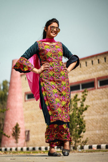 Full length of a smiling young woman standing against building