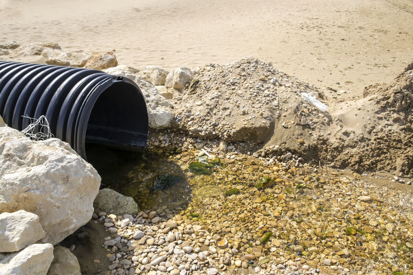 Drains into the Sea Beach Beauty In Nature Close-up Day Drain Environment Environmental Pollution Idyllic Nature No People Non-urban Scene Outdoors Pipe Pollution Pollution In My World Rock Rock - Object Sand Scenics Sea Shore Stone - Object Tranquil Scene Tranquility Water