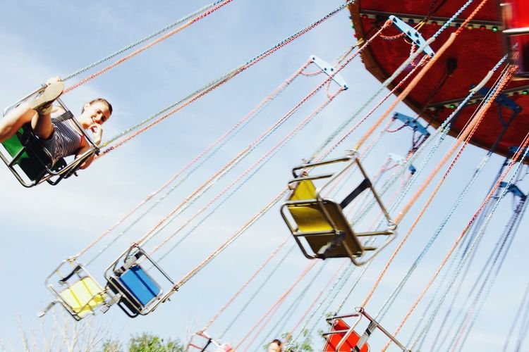 Woman sitting in amusement park ride against clear sky