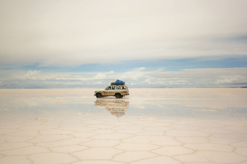 Jeep at Salar De Uyuni Air Vehicle Beauty In Nature Cloud - Sky Day Distant Dramatic Sky Flying Journey Majestic Mid-air Mode Of Transport Nature Non-urban Scene Paving Stone Scenics Sky Tourism Tranquil Scene Tranquility Transportation Travel Travel Destinations