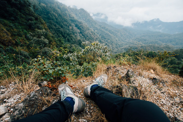 Low section of man wearing shoes on cliff