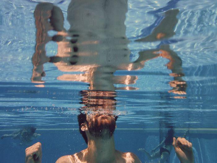 Shirtless Man Swimming In Pool