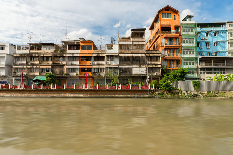 Narrow Terraced housing over looking a canal waterway in central Bangkok, Thailand. ASIA Asian  Bangkok Bright Brown Water City Life Cityscape Colourful Flowing Flowing Water Iced Coffee Narrow Terrace Thai Thailand Canal City Scape Homes Housing River Tall Waterway