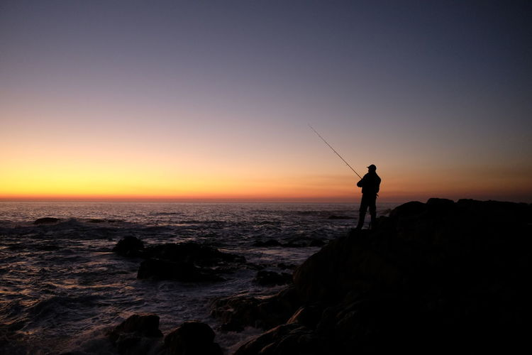 Silhouette man fishing at beach against clear sky during sunset