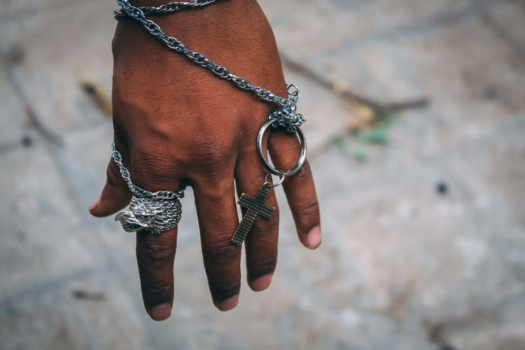 Cropped hand holding crucifix outdoors