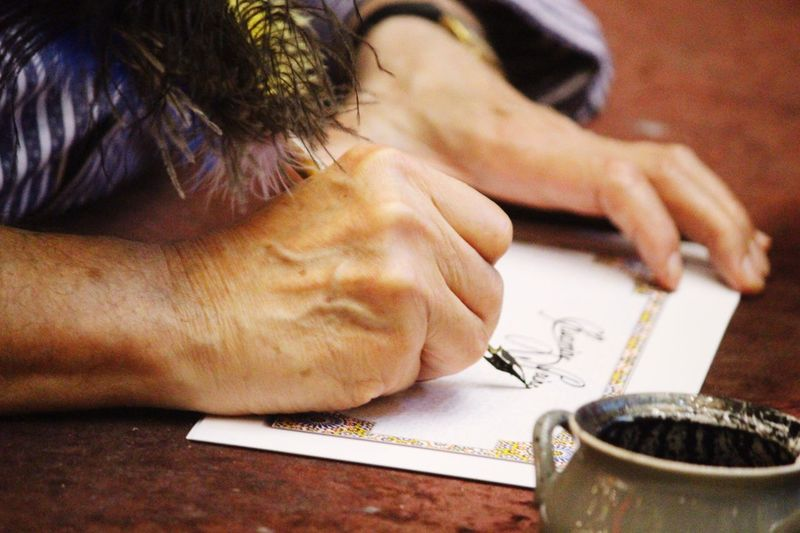 Cropped image of woman writing on paper with fountain pen on table