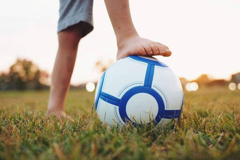 Low Section Of A Boy Holding Ball Under Foot