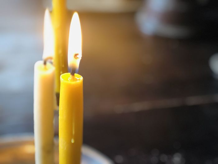Close-up of lit candle in temple