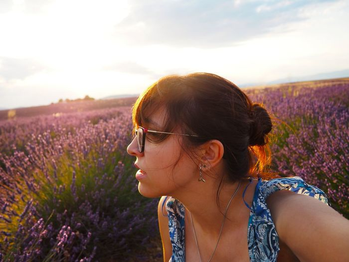 Portrait of woman with pink flowers on field against sky