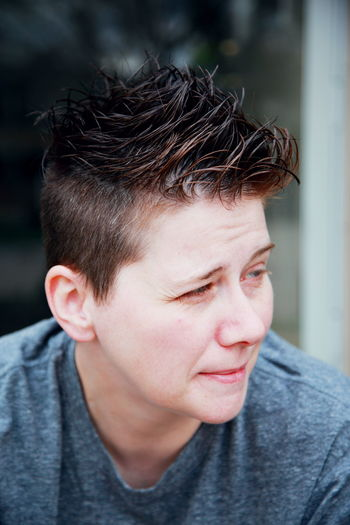 Close-up portrait of lesbian with furrowed eyebrows and cool hair