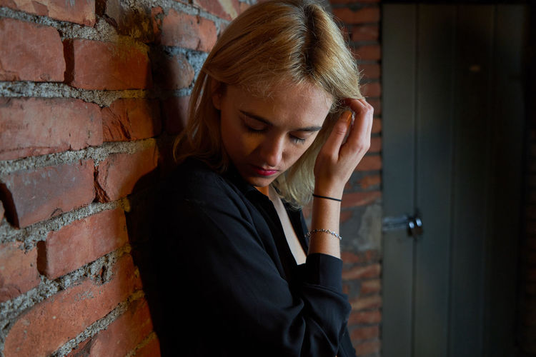 Sensuous woman standing against brick wall