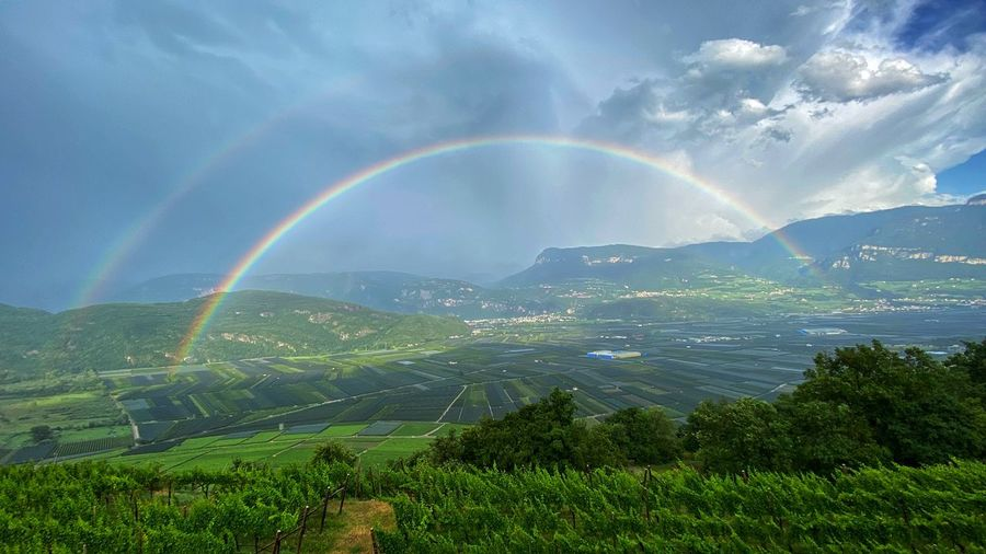 Scenic view of rainbow over landscape against sky