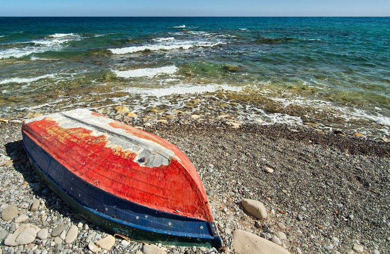Old boat on shore at sea Pebble Beach Surf Beach Blue Boat Day Fishing Boat Greece Horizon Over Water Mirtos Mirtos, Crete Nautical Vessel No People Ocean Outdoors Pebbles Red Bluff Rocks Sand Scenics Sea Shore Shoreline Sky Water