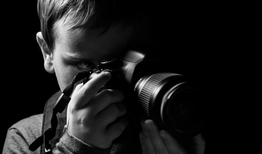 Close-up of boy photographing with camera against black background