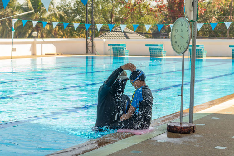 Instructor teaching swimming to boy in pool