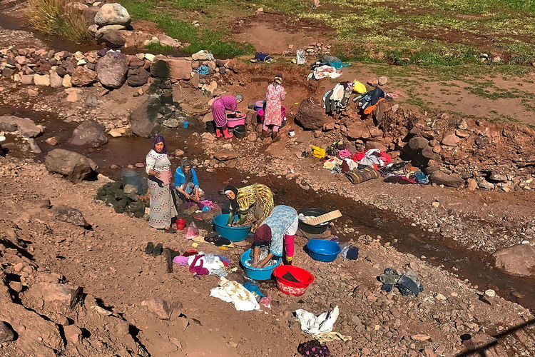 Washing day at Ighrem N'Ougdal in Morocco. Clothes Day Grass Ighrem N'Ougdal Morocco Multi Colored Outdoors Plastic Pots River Sand Stones Washing Day Water Heater Women
