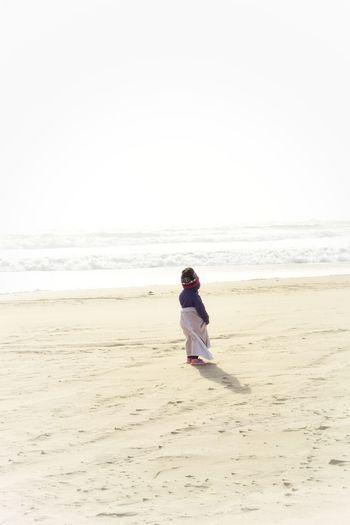 Child standing face towards ocean