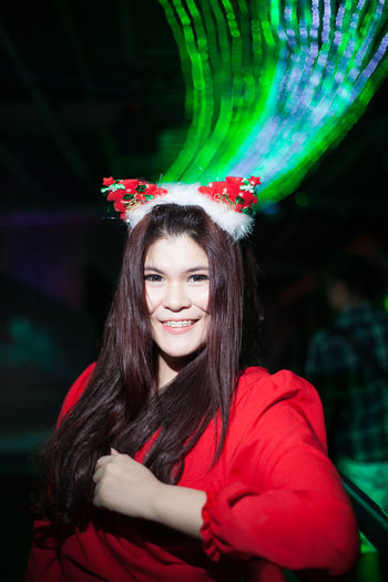 Portrait of smiling young woman wearing headwear at night