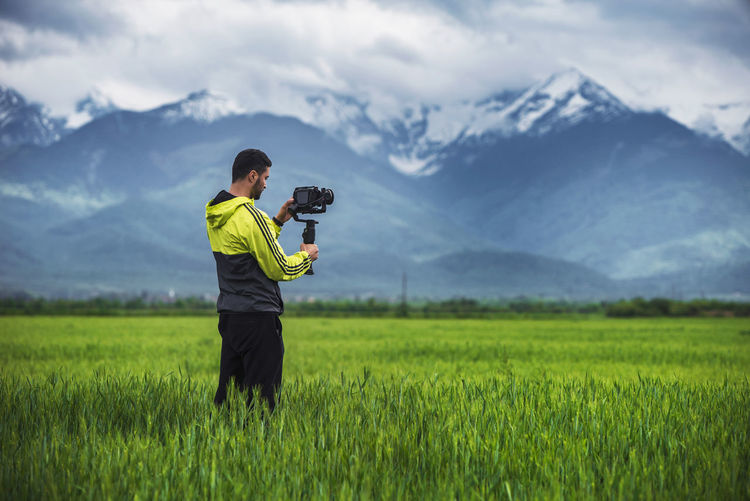 Full length of man photographing on field