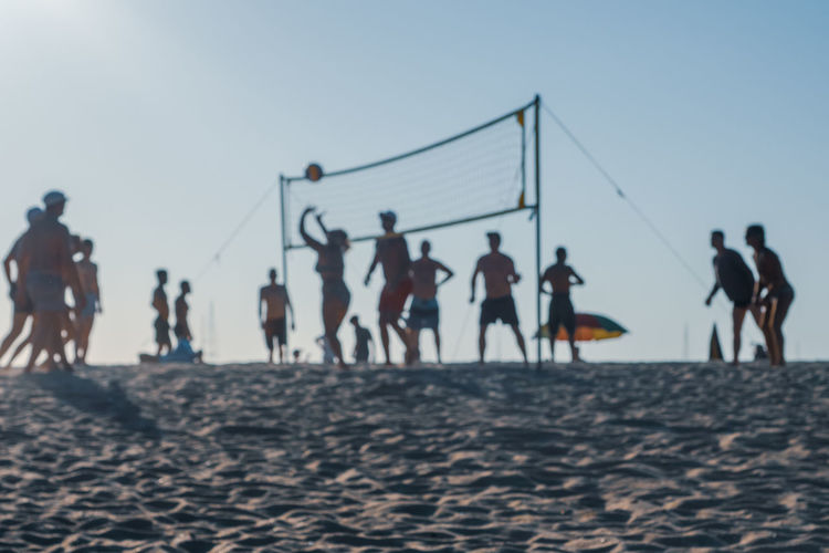 People playing on beach against clear sky
