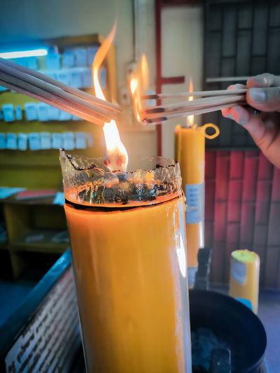 Close-up of hand holding lit tea light candles