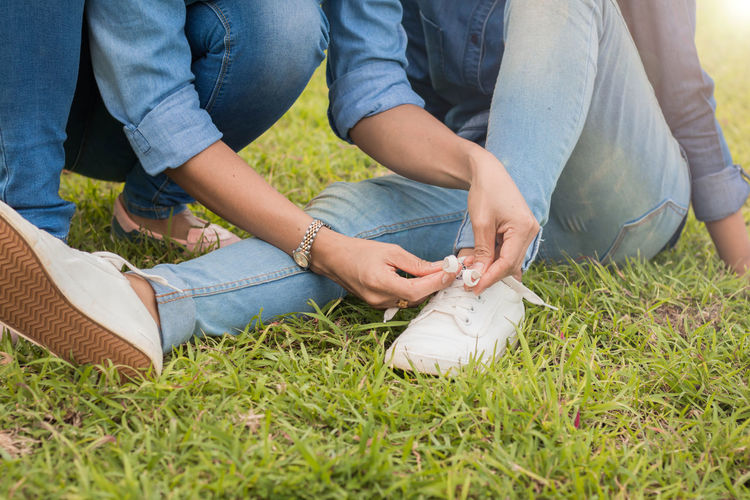 Low section of female friends wearing shoes on grass