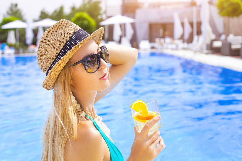 Portrait of young woman wearing sunglasses in swimming pool