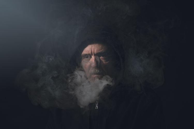 Portrait of man smoking against black background
