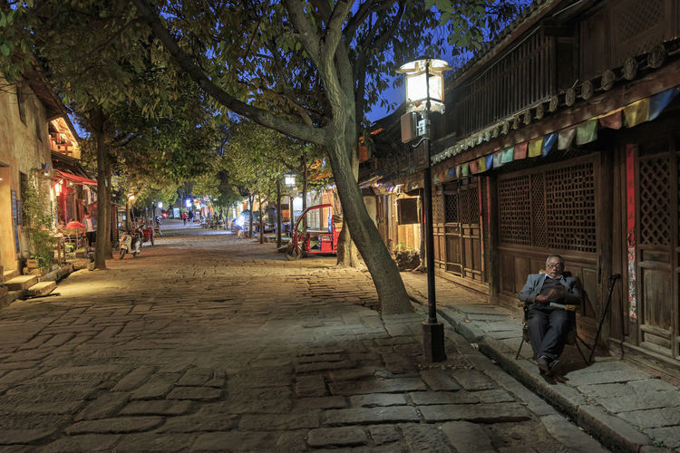 Shaxi, China - February 21, 2019: Chinese man reasting on a chair in the central square of Shaxi old town at dusk Shaxi China ASIA Yunnan Yunnan ,China Market South Silk Road Tea Horse Road Minority Ethnic Group Old Town Kunming, China Landscape People Night Teather Old