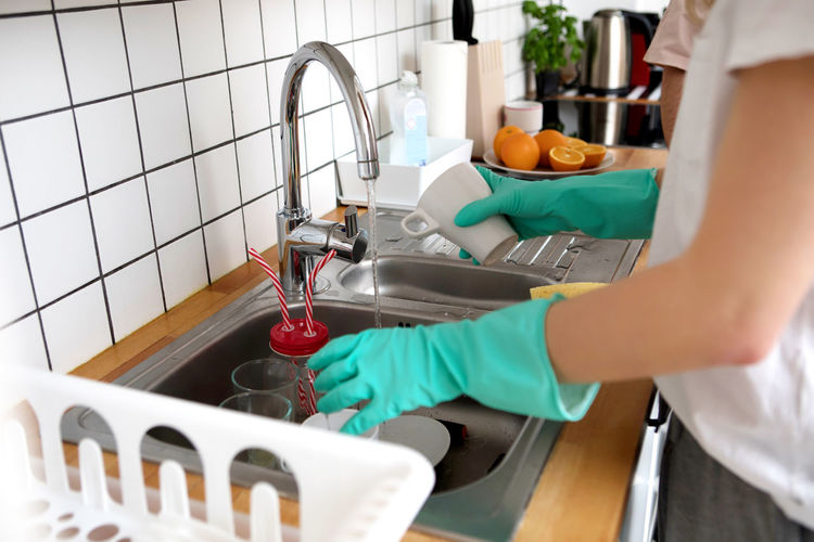 Midsection of woman working in kitchen at home