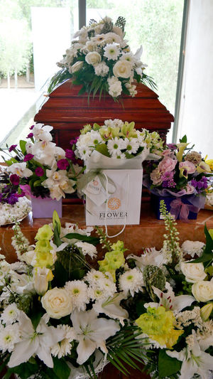closeup shot of a colorful casket in a hearse or chapel before funeral or burial at cemetery Burial Candle Cemetery Chapel Death Casket Caskett Coffin Farewell Flower Funeral Goodbye Grieving Heart Insurance Mourning Dove Old Age Old Age People Sadness