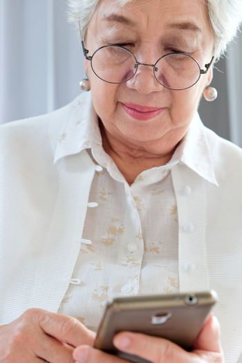 Close-up of woman using mobile phone indoors
